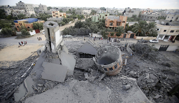 Palestinians gather around the remains of a mosque, which witnesses said was destroyed in an Israeli air strike before a 72-hour truce, in Khan Younis