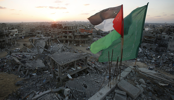 A Palestinian flag and a Hamas flag flutter atop the wreckage of a house in the east of Gaza City